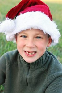 Young boy missing his two front teeth wearing a red Santa Clause hat.