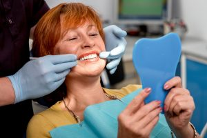 Dentist fitting dentures on patient